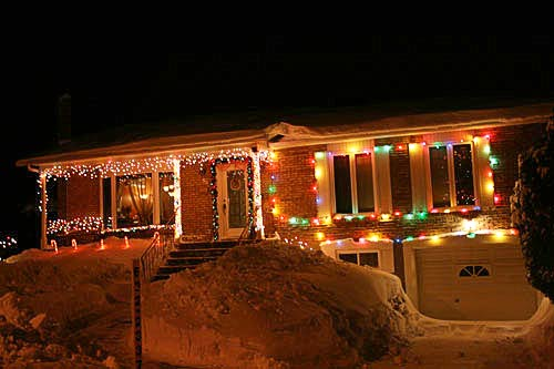 house in heavy snows banks decorated with christmas lights