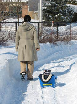my wife pulling our son in a snow sled