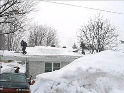 shovelling snow off a roof during the middle of winter