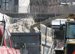 close up of snow being thrown from snowblower into dumptruck